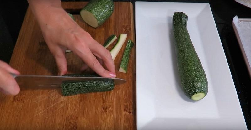 Нарежете тиквички и включете фурната на 220 градуса.