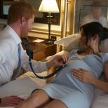Хари слуша със слушалката пулса на детето и след това измерва корема на жена си.