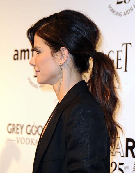 Сандра Бълок с чуплива коса в средно ниска опашка и пуснат бретон настрана