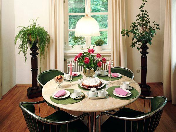 Малка трапезария с кръгла маса и метални столове с възглавнички