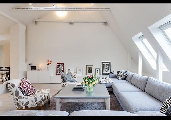 дневна с голям диван в компактна мансарда в Стокхолм