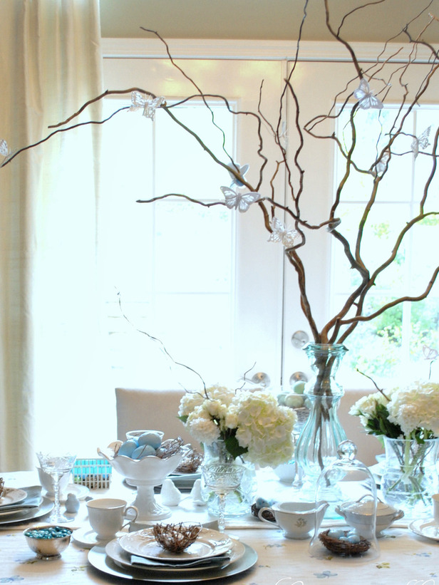 Празнична украса на масата за Великден с бели цветя и клонки
