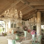 Кухня в бяло с пищни полилеи и щъркели от ковано желязо
