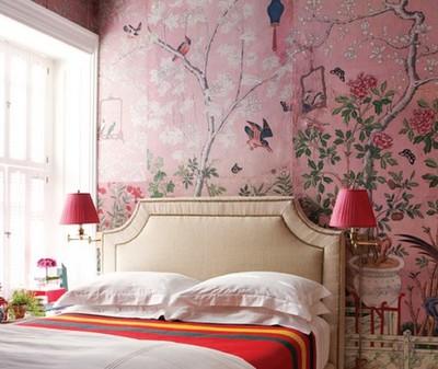 Интериор спалня с бяло легло, розови лампи и фототапет разцъфнало дърво