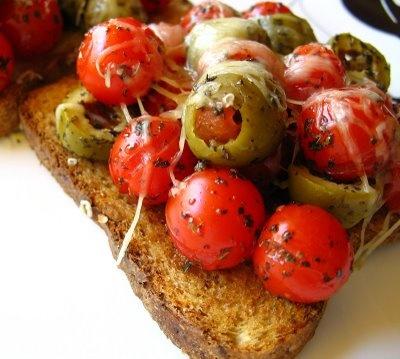 Брускета с цели чери доматчета и зелени маслини, поръсени с босилек и пармезан