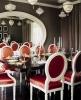 Интериор за трапезария с черна голяма правоъгълна маса и червени столове с бели рамки