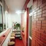 Остъклен балкон със стена от тухли и високи столчета